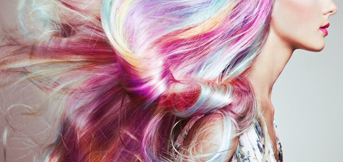 Profile of woman with pastel rainbow hair and cheekbone with highlight
